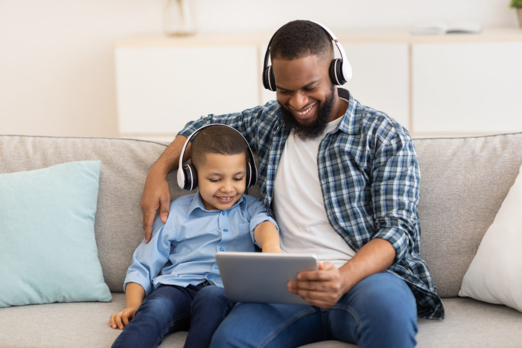 Dad And Son Using Tablet Wearing Earphones Sitting Indoors